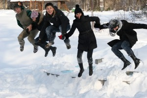 Happy people jumping together in the snow